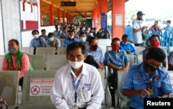 People wearing protective masks sit as they queue for their turn to receive a dose of the AstraZeneca coronavirus disease (COVID-19) vaccine during the mass vaccination program for transportations workers at Kampung Rambutan bus station in Jakarta, Indonesia