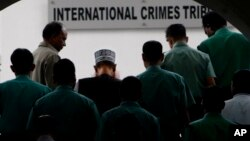 FILE - Bangladeshi police officers escort Delwar Hossain Sayeedi, center with cap, a leader of Bangladesh's largest Islamic party Jamaat-e-Islami, as he comes out after appearing before a special tribunal in Dhaka, Bangladesh, Monday, Nov. 21, 2011.
