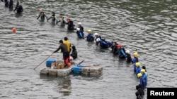Nhân viên cấp cứu tìm kiếm nạn nhân gần địa điểm chiếc máy bay TransAsia bị rơi tại Tân Bắc, 6/2/2015.