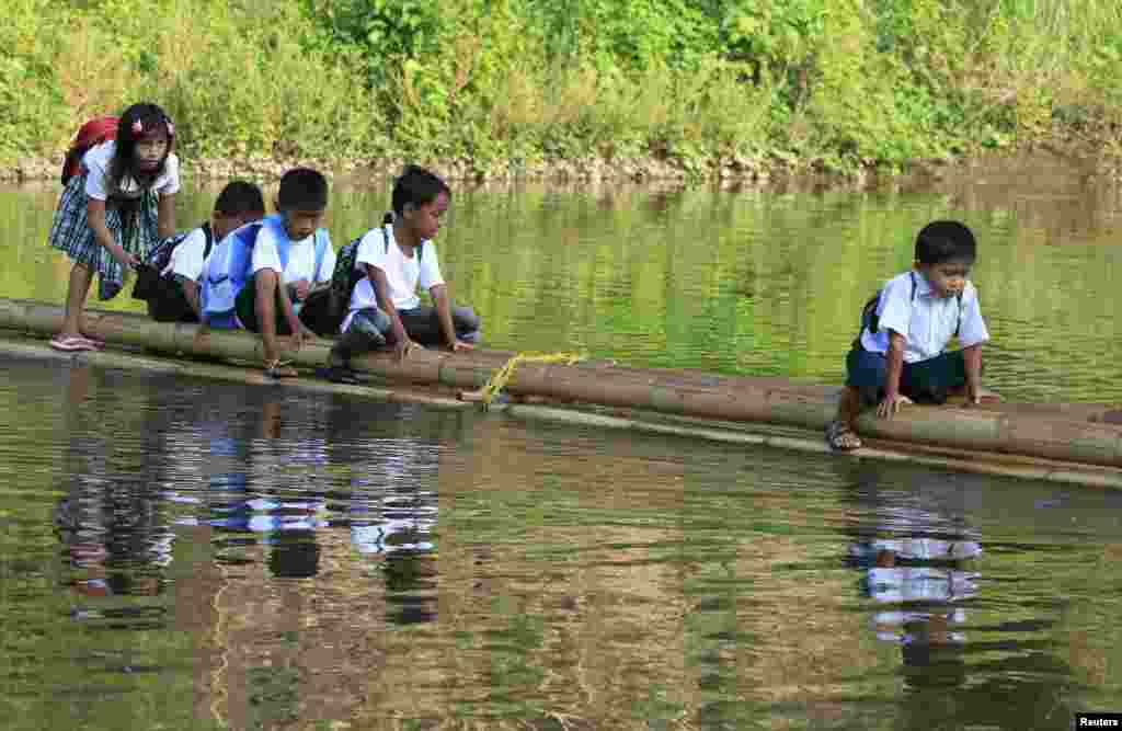Students sit astride on a bamboo raft as they are ferried across a river on their way to Casili Elementary School for the first day of classes in Rodriguez, Rizal province, east of Manila, Philippines.