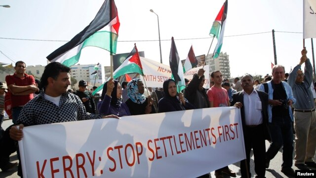 Palestinians protesters hold a banner during demonstation in the West Bank town of Bethlehem, Nov. 6, 2013.