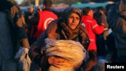 一名从反政府武装控制的阿勒颇东城区转移出来的平民抱着大饼和其他人一道抵达叙利亚反政府武装控制的拉西迪恩镇。(2016年12月15日)