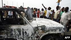 Sinh viên Côte d'Ivoire biểu tình gần một chiếc xe của Liên Hiệp Quốc bị đốt cháy ở Abidjan, 13/1/2011