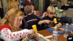 FILE - Idaho Arts Charter School students Maddison Thorpe, left, and Stefan Weiss work on their leather crafts as nationally known leather artist Deana Attebery shows the students the different kinds of tools of the trade in Nampa, Idaho, Dec. 9, 2008. The school received a National Endowment for the Arts grant to hold a series of folk arts after-school enrichment classes for at risk youths.