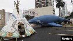 Para pengunjuk rasa mendirikan tenda tradisional (Teepee) bergambar paus dan lumba-lumba di dekat balon berbentuk paus, di depan gedung tempat pelaksanaan konferensi Komisi Ikan Paus Internasional (IWC) di kota Panama (4/7).