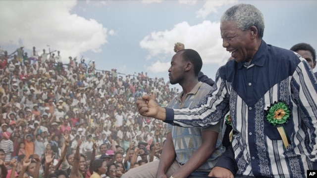 Then-African National Congress President Nelson Mandela salutes the crowd in Galeshewe Stadium near Kimberley, South Africa, Feb. 25, 1994.