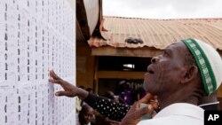 Un homme cherche son nom sur une liste avant de s'enregistrer et de voter en plaçant son bulletin de vote dans l'urne plus tard dans la journée à Lagos, au Nigeria, samedi 28 mars 2015.
