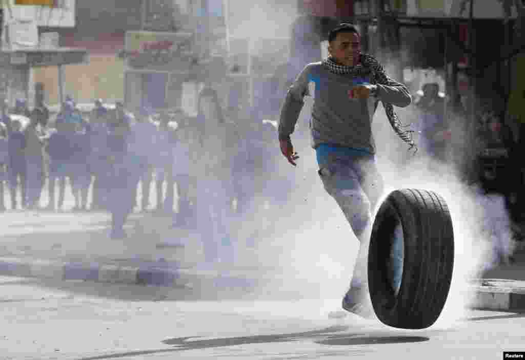 A Palestinian protester kicks a burning tire during clashes with Israeli troops following an anti-Israel demonstration in the West Bank city of Hebron, Nov. 14, 2014.