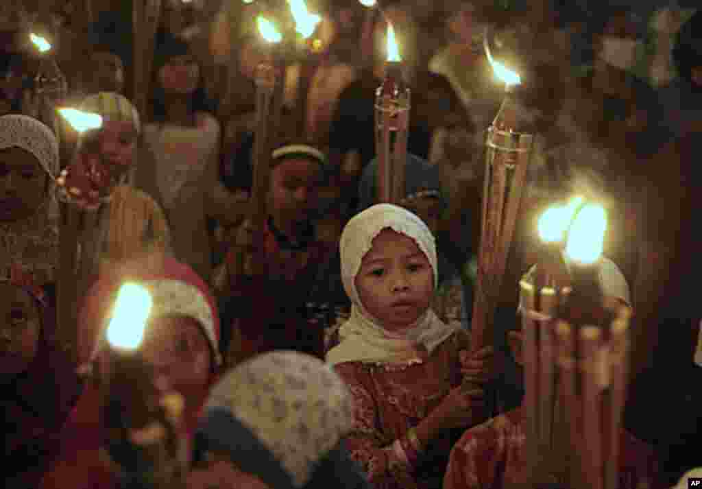 Indonesian Muslim children carry torches during a parade celebrating Eid al Fitr holiday that marks the end of the holy month of Ramadan in Jakarta, Indonesia, Aug. 30, 2011. AP