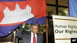 UN special rapporteur Surya Subedi walks through a Cambodian national flag upon his arrival in a conference room at the UN headquarter in Phnom Penh.
