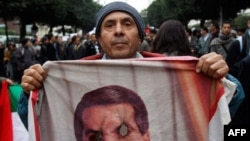 A protestor holds a burn picture of former Tunisian President Zine El Abidine Ben Ali during a demonstration in Tunis, Tuesday, Jan. 25. 2011. Hundreds of Tunisian protesters are demonstrating outside the prime minister's office to demand the removal of