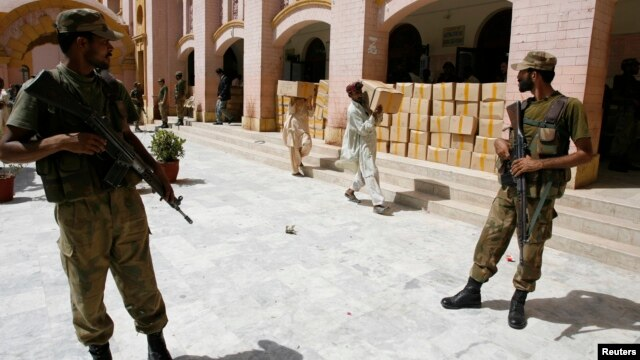 Pakistani soldiers stand guard outside a district court as election commission workers carry election materials in Hyderabad, May 8, 2013.