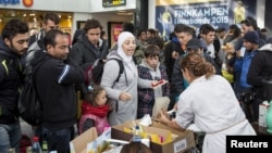 Volunteers distribute food and drinks to migrants who arrived at Malmo train station in Sweden on the morning of Sept. 10, 2015.