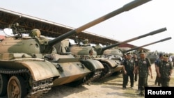 Cambodia's Deputy Prime Minister and Defence Minister Tea Banh (2nd R) inspects tanks inside the Army Institute after a graduation ceremony at Army Institute in Kampong Speu province March 12, 2015.