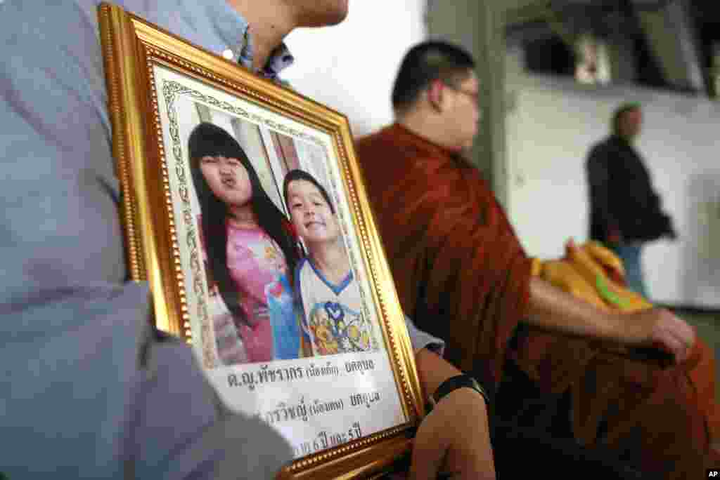 Tayakorn Yos-ubon, left, the father of two children killed in a bomb attack on Feb. 23 at an anti-government protest site, holds their portrait as he waits with a monk for their bodies at a hospital in Bangkok, Feb. 24, 2014.