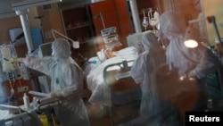 Para petugas medis merawat seorang pasien Covid-19 di rumah sakit Casalpalocco, Roma, Italia.