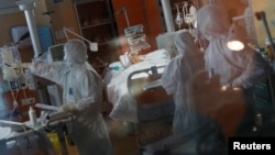 Para petugas medis dengan pakaian pelindung merawat pasien yang terinfeksi virus corona di sebuah rumah sakit (foto: ilustrasi).