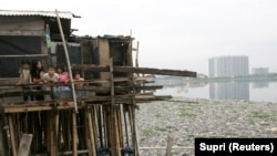 Anak-anak berdiri di dalam rumahnya di atas danau yang tercemar sampah di kawasan kumuh, Jakarta Utara. Presiden Joko Widodo meminta kemiskinan di Tanah Air dientaskan pada 2024. (Foto: REUTERS/Supri)