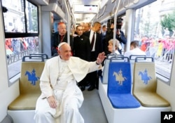 Pope Francis waves to a cheering crowd of faithful as he drives by in a public transportation tram he used to reach the venue of the World Youth Days in Krakow, July 28, 2016.