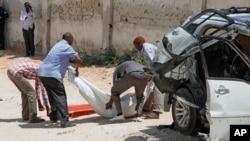 Le corps de l'ancien ministre de la Défense somalien Muhyadin Mohamed Haji porté par des secours au lieu où une bombe placée dans sa voiture a explosé à Mogadiscio, Somalie, 15 février 2016.