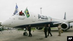 FILE - Azul airline official sprays champagne on company's first aircraft at the airport in Rio de Janeiro, Sept. 17, 2008.