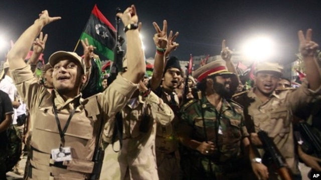 Fighters with Libya's interim government celebrate at Martyrs' Square in Tripoli October 20, 2011.