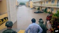 Soldados y civiles observan una calle inundada en Chilpancingo, México.