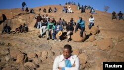 "Miners gather at a hill known as the ""Hill of Horror"" ahead of the one-year anniversary commemorations to mark the killings of 34 striking platinum miners shot dead by police outside the Lonmin's Marikana platinum mine in Rustenburg, South Africa, Aug. 16"