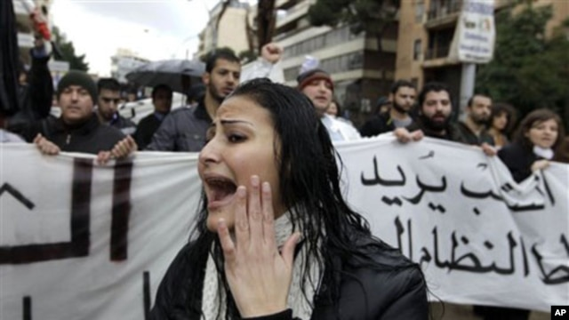 A woman shouts slogans as protesters behind her carry a banner condemning Lebanon's current sectarian system of government, Beirut, February 27, 2011