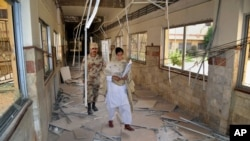 FILE - A Pakistani paramilitary soldier and a nurse walk through a corridor at the Bolan Medical complex damaged by an attack claimed by the Sunni militant group Lashkar-e-Jhangvi, in Quetta, Pakistan, June 16, 2013. Masroor Nawaz Jhangvi, son of Lashkar-e-Jhangvi's slain founder, has won the Jhang district by-election for a seat in the Punjab Assembly.