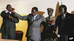 Zimbabwean President Robert Mugabe, centre, holds the hands of Morgan Tsvangirai, leader of the main opposition party, right, and Arthur Mutambara, leader of the other faction of the opposition party, at the signing of a memorandum of understanding betwee