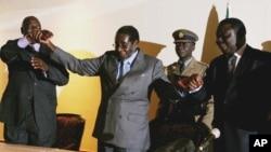 Zimbabwean President Robert Mugabe, centre, holds the hands of Morgan Tsvangirai, leader of the main opposition party, right, and Arthur Mutambara, leader of the other faction of the opposition party, at the signing of a memorandum of understanding betwee