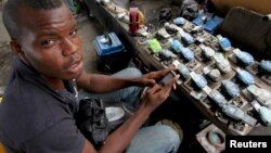 FILE - Jamil Idriss charges 50 naira ($0.33) to recharge phone batteries using rows of three-pin sockets nailed to a plank of wood and plugged into a diesel generator in the Obalende district of Lagos, Nigeria, May 20, 2010.