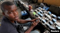 A Nigerian man uses a small generator to charge wireless phones for a small fee.