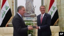 18일 이라크를 방문한 애슈턴 카터 미 국방장관(오른쪽)이 칼레드 알-오베이디 이라크 국방장관과의 회담에 앞서 선물을 받고 있다.