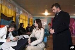 """Діючий лідер самопроголошеної """"Донецької народної республіки"""" Денис Пушилін, праворуч, та його дружина чекають, щоб отримати виборчі бюлетені на виборчій дільниці під час сепаратистських виборів у Донецьку, 11 листопада 2018 року."""