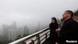ບັນດານັກທ່ອງທ່ຽວ ຈາກຈີນແຜ່ນດິນໃຫຍ່ ພາກັນຊົມທ້ອງຟ້າ ທີ່ເຕັມໄປດ້ວຍໝອກກົ້ວ ຢູ່ເທິງພູ the Peak ໃນຮົງກົງ.