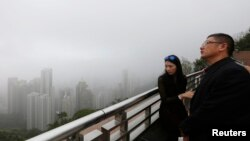 Mainland Chinese visitors look at the foggy skyline of Hong Kong island from the Peak in Hong Kong, Feb. 24, 2015.