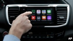 FILE - Chris Martin from Honda North America demonstrates Apple CarPlay, which lets drivers use an iPhone and its voice-activated assistant, Siri, to operate some of their vehicle's electronic controls and entertainment systems, in Torrance, Calif., August 20, 2015.