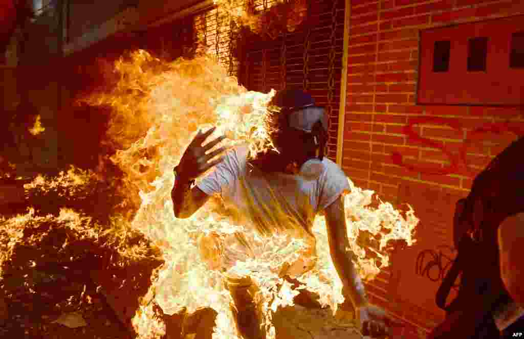 A demonstrator catches fire during clashes with riot police duing a protest against Venezuelan President Nicolas Maduro, in Caracas, May 3, 2017.
