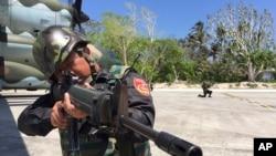 Cảnh sát biển Đài Loan cạnh máy bay vận tải quân sự C-130 trên đường băng của đảo Ba Bình, thuộc quần đảo Trường Sa, khoảng 1600 km. (1000 dặm) về phía nam của Đài Loan, ngày 23/3/2016.