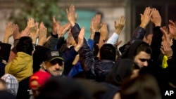 People raise their hands and shout slogans in Bucharest, Romania, during another day of protests calling for better governance and an end to corruption, Nov. 7, 2015.