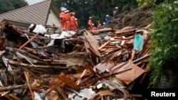 日本消防人員在廣島安佐南區冒雨搜尋生還者。 8月22日發生的山體滑坡沖毀了這個住宅區。