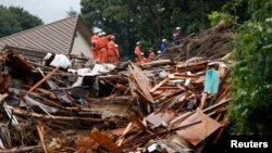 Firefighters search for survivors in the rain at a site where a landslide swept through a residential area at Asaminami ward in Hiroshima, western Japan, August 22, 2014.