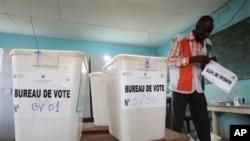 Petugas di sebuah TPS mempersiapkan ruangan sebelum pemungutan suara dimulai di wilayah Cocody, Abidjan (21/4). Saat ini petugas pemilu mulai menghitung hasil perolehan suara yang masuk, yang diperkirakan diikuti hanya 30 persen dari keseluruhan warga Pantai Gading yang memenuhi syarat untuk memilih.