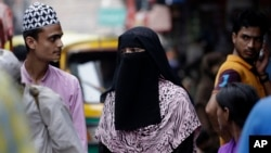 FILE - An Indian Muslim woman walks at a market area in New Delhi, India, Aug. 22, 2017. India's Supreme Court on Tuesday struck down the triple talaq Muslim practice that allows men to instantly divorce their wives as unconstitutional.
