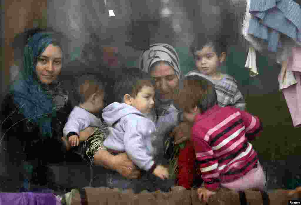 Syrian refugees look through a window inside a refugee center as they wait for a distribution of humanitarian aid by volunteers of the Bulgarian Red Cross in Sofia.