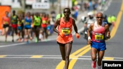 Boston Marathon elite runners Josphat Boit (left) and Meb Keflezighi (right) race to the finish line during the 2014 Boston Marathon in Massachusets, USA.