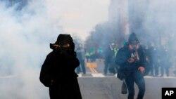 Un manifestante protege su boca y nariz contra el gas disparado por la policía durante una manifestación después de la inauguración del presidente Donald Trump el viernes 20 de enero de 2017 en Washington.