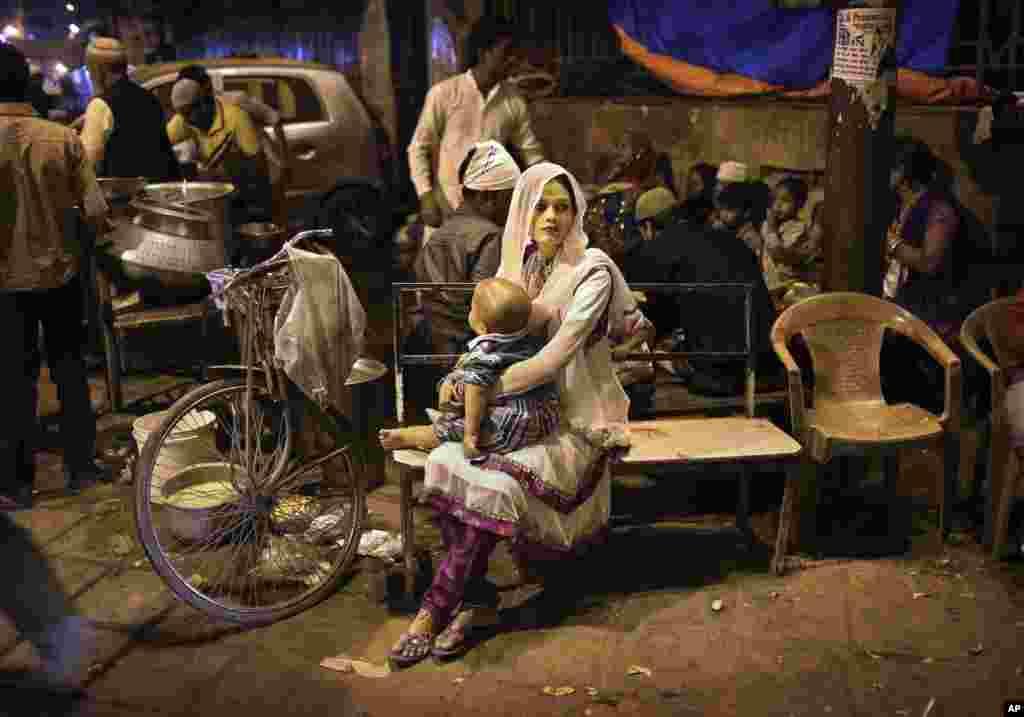 Một phụ nữ Hồi Giáo Ấn Độ bế con ngồi chờ trên một ghế dài tại một quán bán thức ăn ở New Delhi.